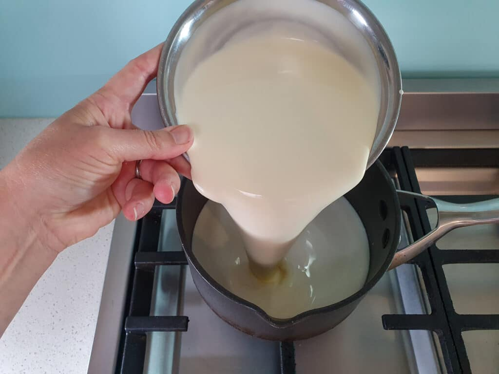 Adding cream to pot on stove.