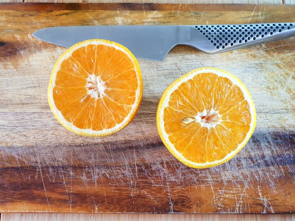 Cutting oranges in half to juice.
