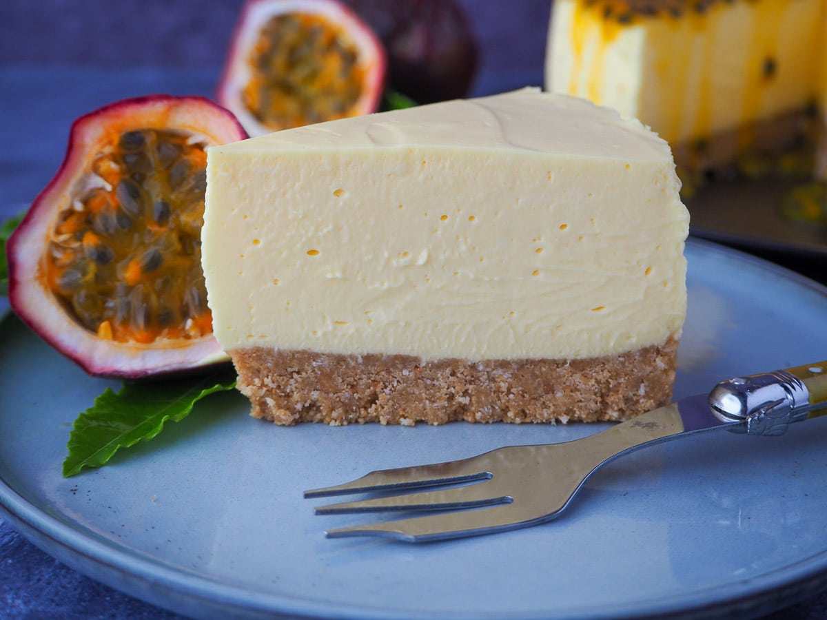 Passion fruit cheesecake on a plate, with a vintage for, fresh passion fruit and leave on the side, and the rest of the cake in the background.