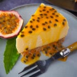 Close up passion fruit cheesecake with passion fruit coulis, a vintage fork in front, fresh passion fruit and passion fruit leave on the side.