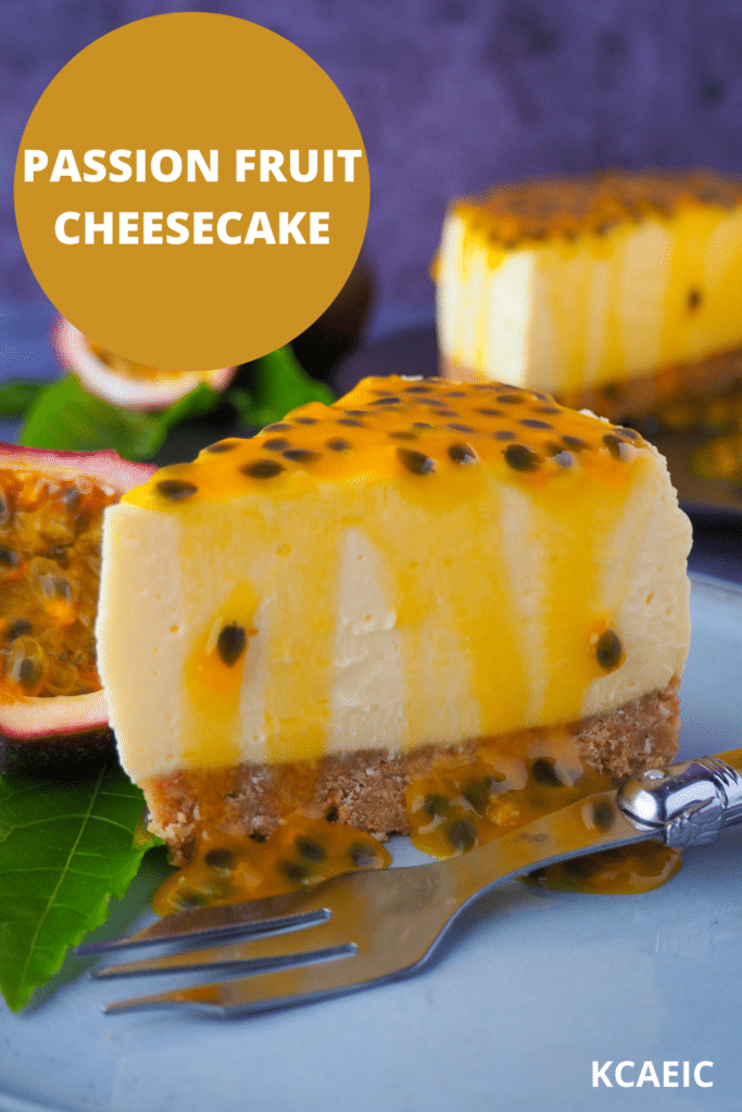 Passion fruit cheesecake with passion fruit coulis, a vintage fork in front, fresh passion fruit and passion fruit leave on the side, and rest of cheesecake in the background, with text overlay passion fruit cheesecake, KCAEIC.