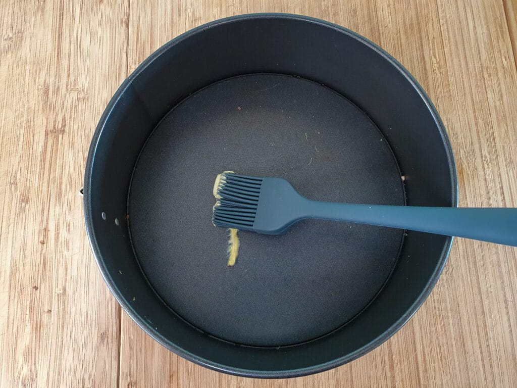 Greasing springform tin before lining with baking paper.