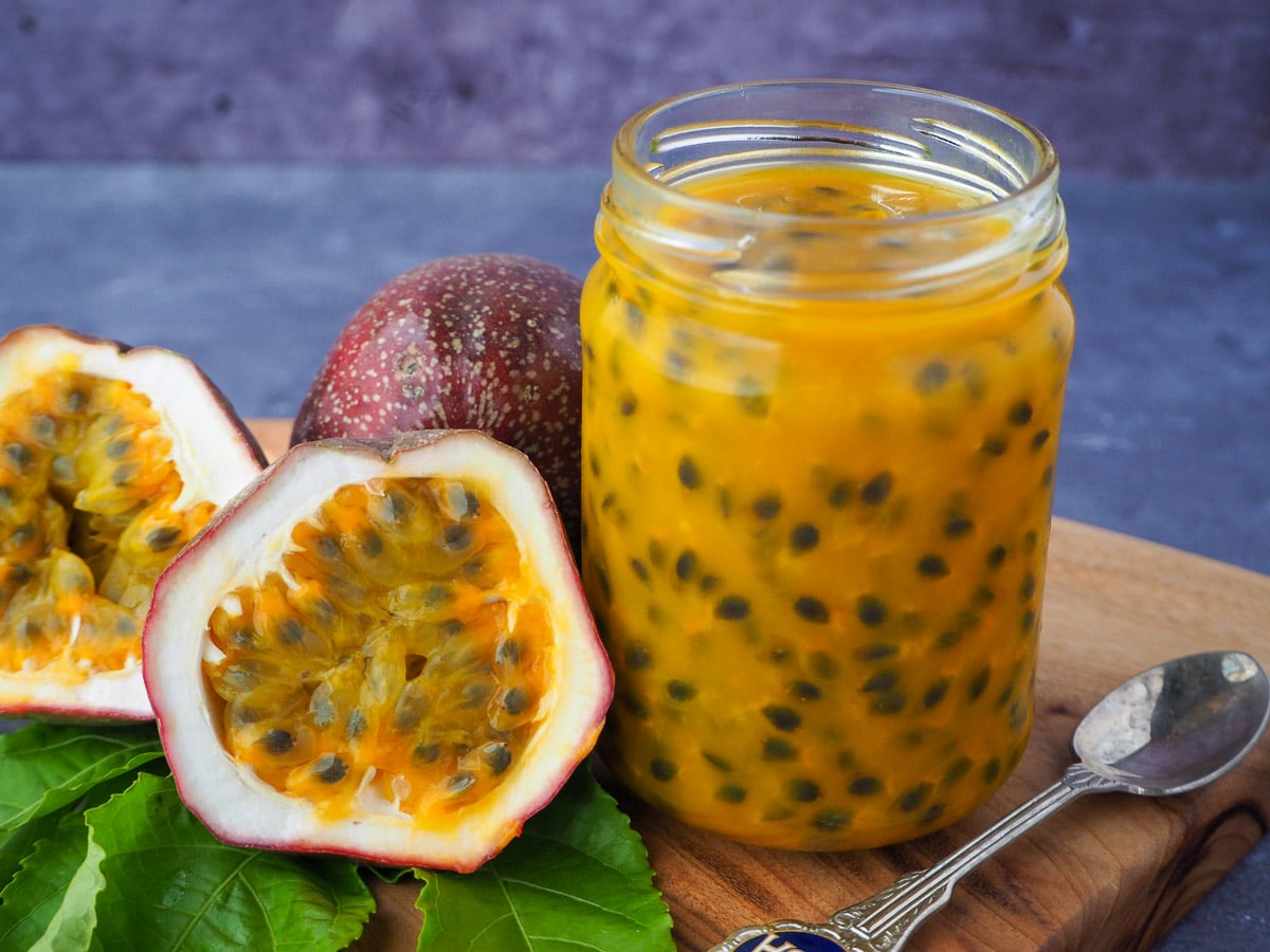 Passion fruit coulis in an open glass jar with a vintage spoon in front and fresh, cut open passion fruit and passion fruit leaves on the side, on a wooden chopping board.