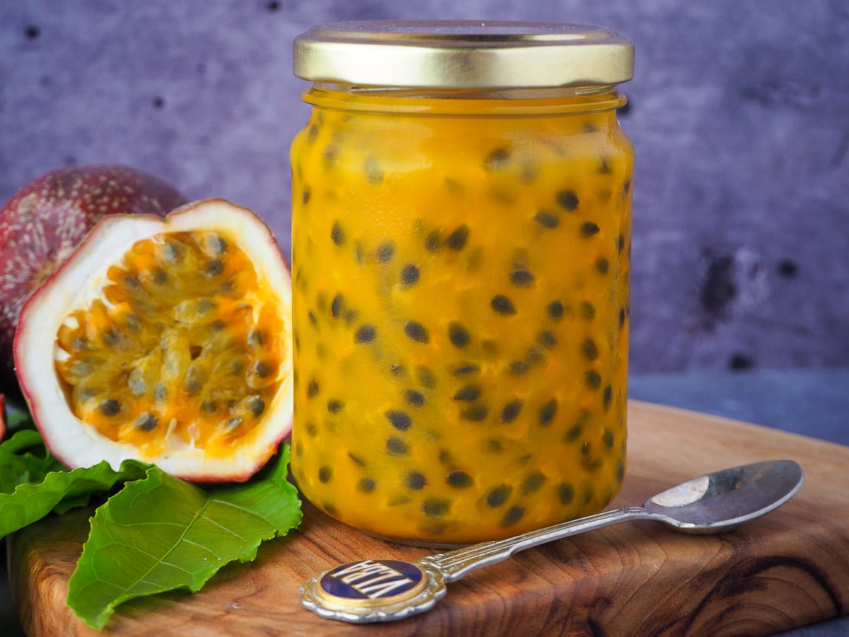 Passion fruit coulis in a glass jar with a vintage spoon in front and fresh, cut open passion fruit and passion fruit leaves on the side, on a wooden chopping board.