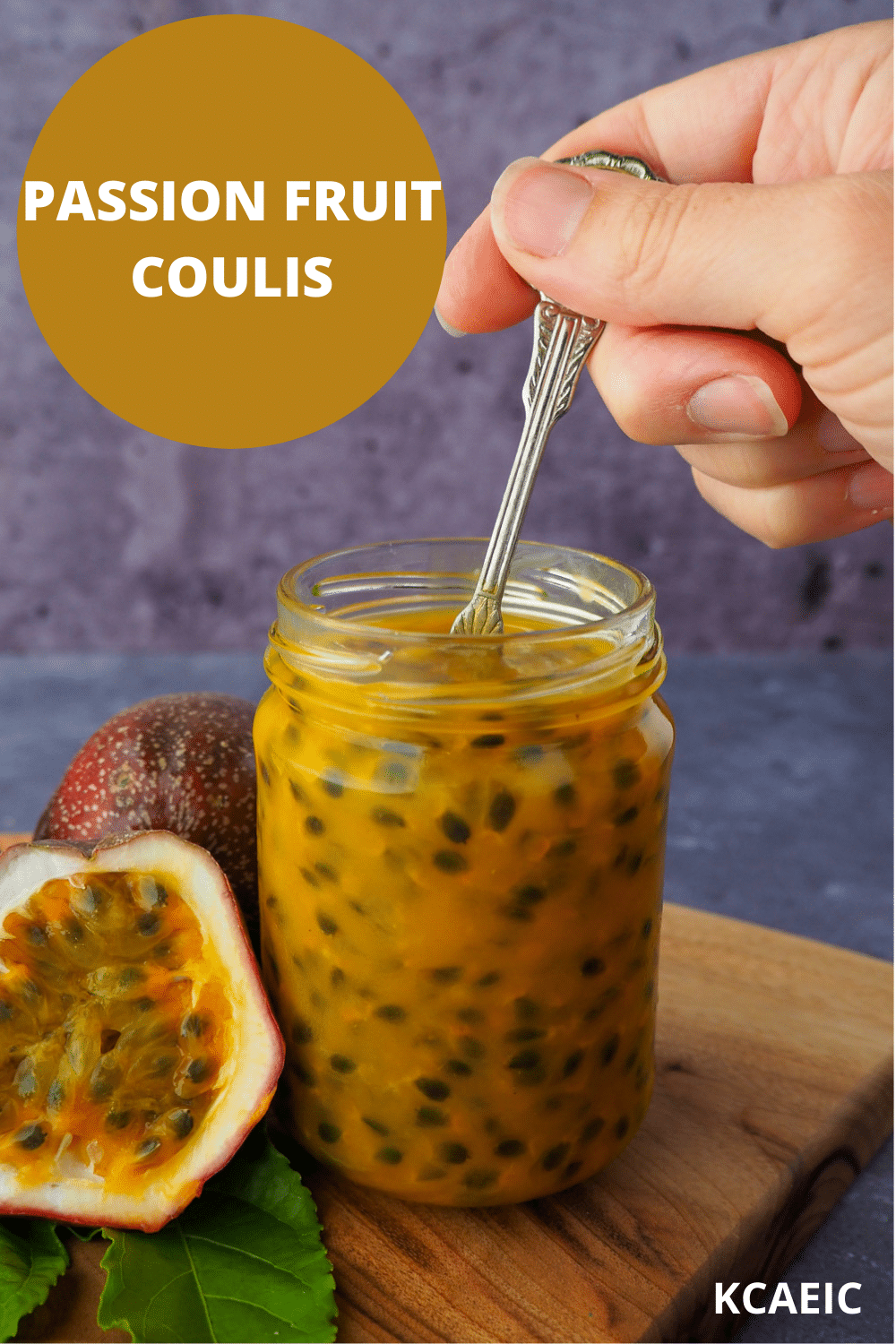 Passion fruit coulis in an glass jar a hand holding a vintage spoon in the jar and fresh, cut open passion fruit and passion fruit leaves on the side, on a wooden chopping board, with text overlay Passion fruit coulis, KCAEIC