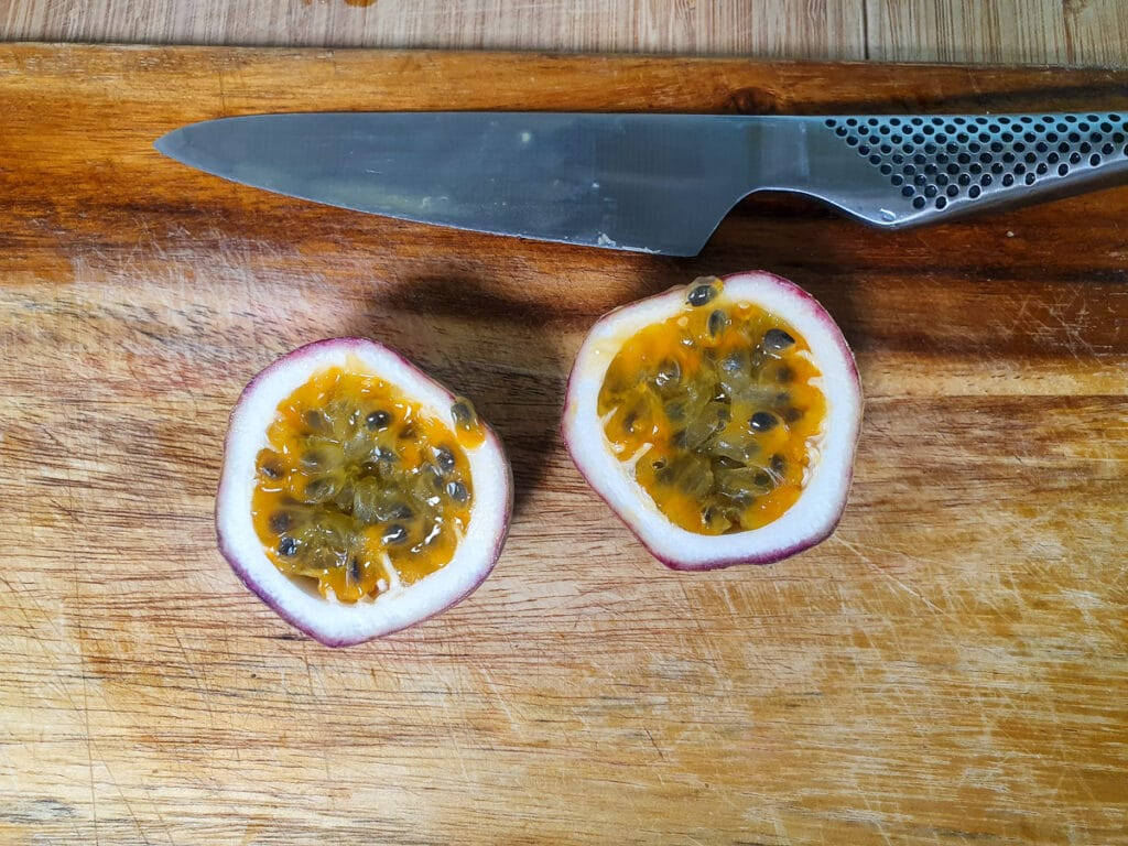 Cutting open passion fruit to scoop out pulp.