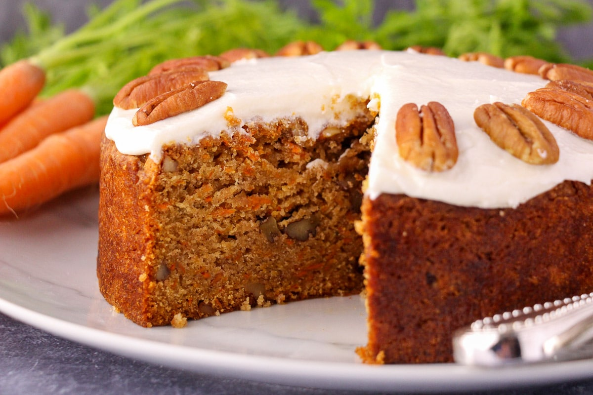 Eggless carrot cake decorated with lemon icing and pecans, with single slice taken out, fresh Dutch carrots and silver serving wear in the background.