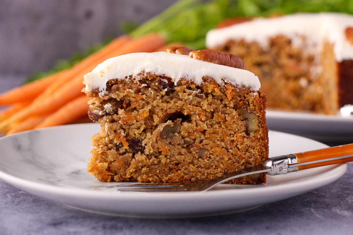 Slice of eggless carrot cake decorated with lemon icing and pecans on a plate with a vintage fork and the rest of the cake and fresh Dutch carrots in the background.
