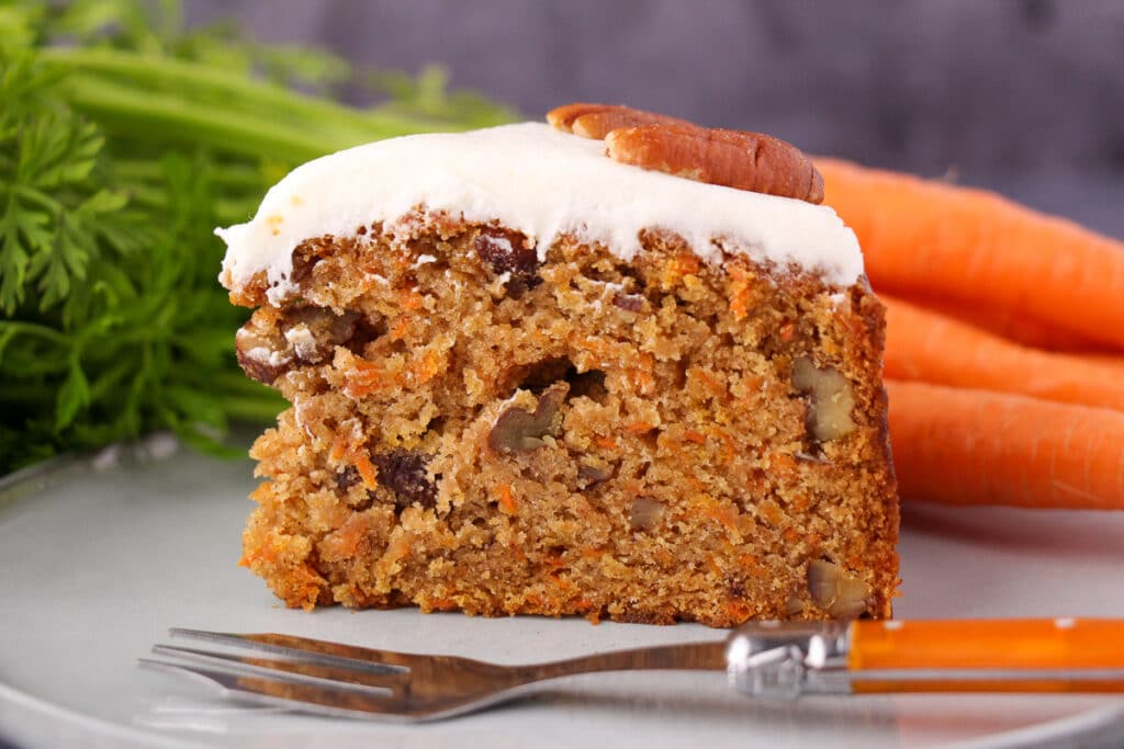 Slice of eggless carrot cake decorated with lemon frosting and pecans, on a plate with a vintage fork and fresh Dutch carrots in the background.