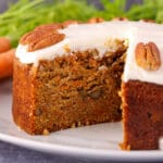 Close up eggless carrot cake decorated with lemon frosting and pecan, with fresh Dutch carrots in the background.