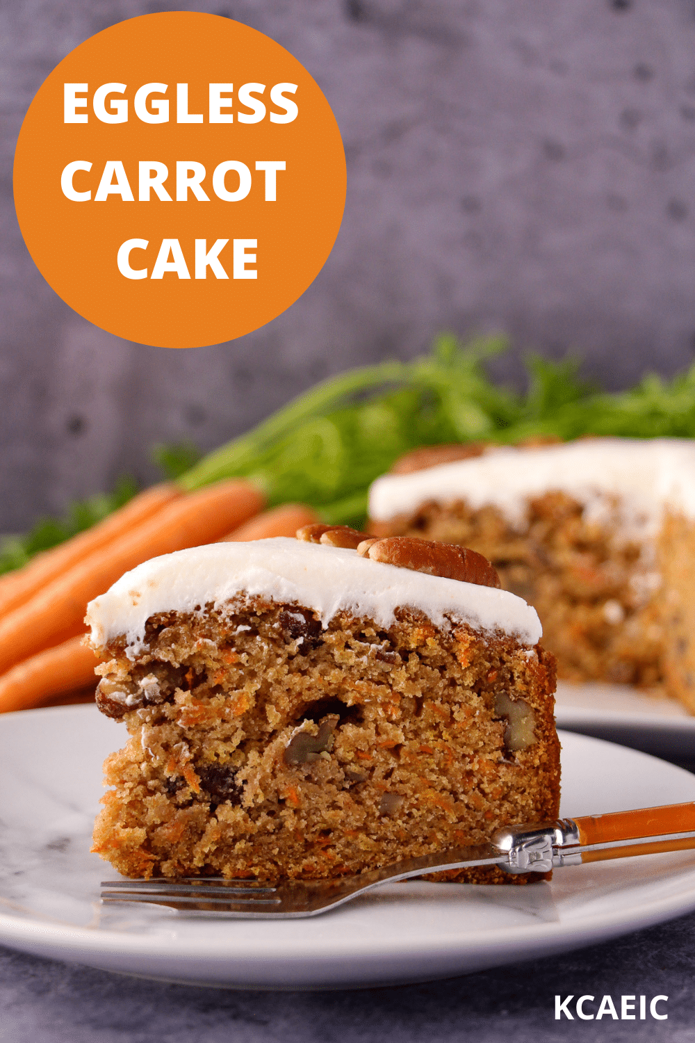 Slice of eggless carrot cake decorated with lemon icing and pecans on a plate with a vintage fork and the rest of the cake and fresh Dutch carrots in the background and text overlay, eggless carrot cake, KCAEIC.