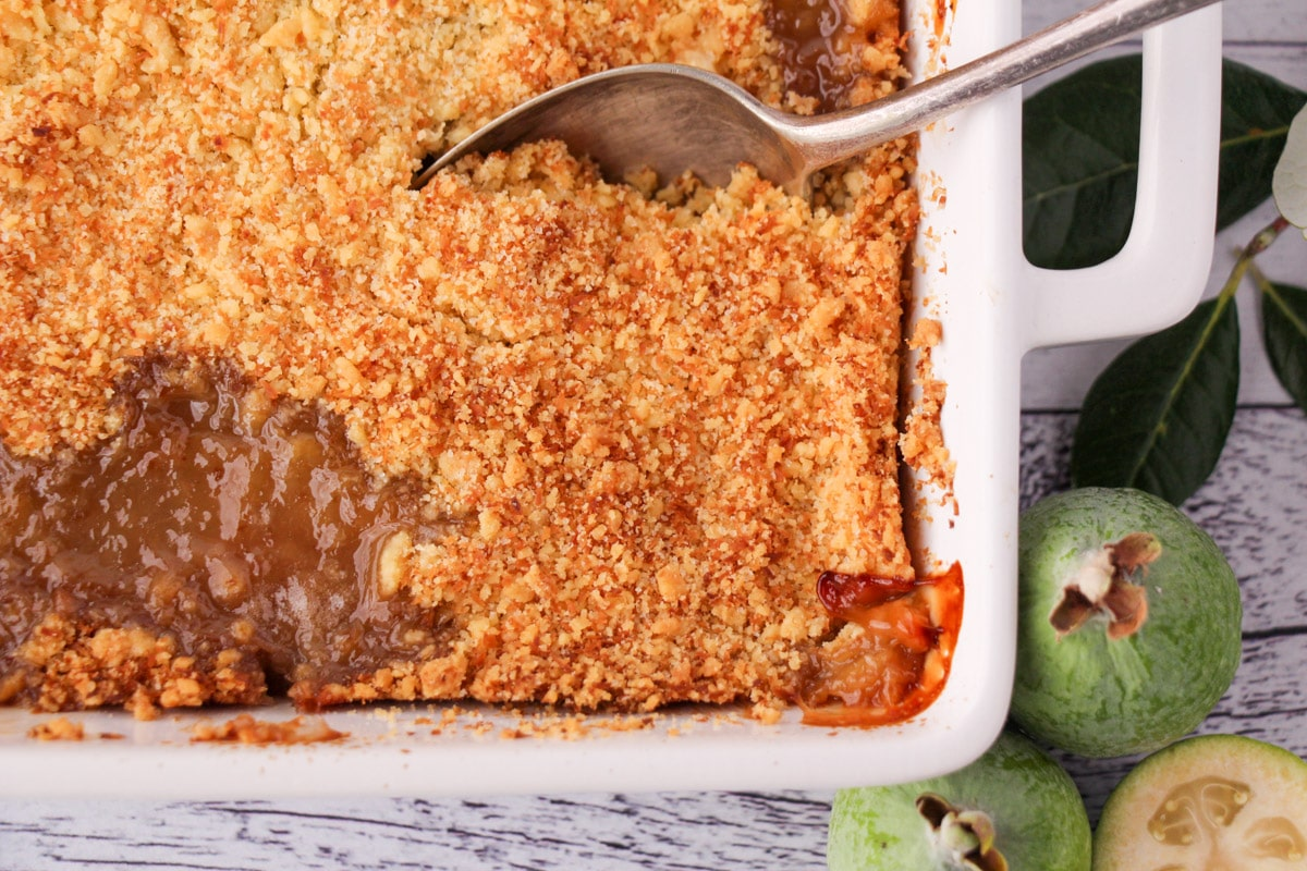 Top down view of feijoa crumble in a baking dish with a vintage serving spoon and fresh feijoa on the side.