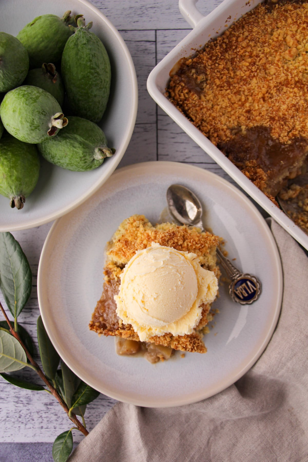 Feijoa crumble on a plate with a scoop of ice cream on top, vintage spoon on the side and fresh feijoas and baking dish of crumble on the sides.