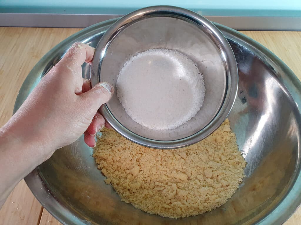 Adding desiccated coconut to flour mix.