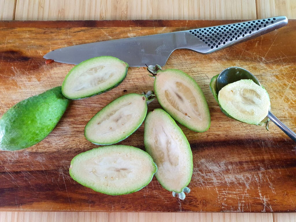 Cutting open feijoas lengthways and scooping out flesh with a teaspoon.
