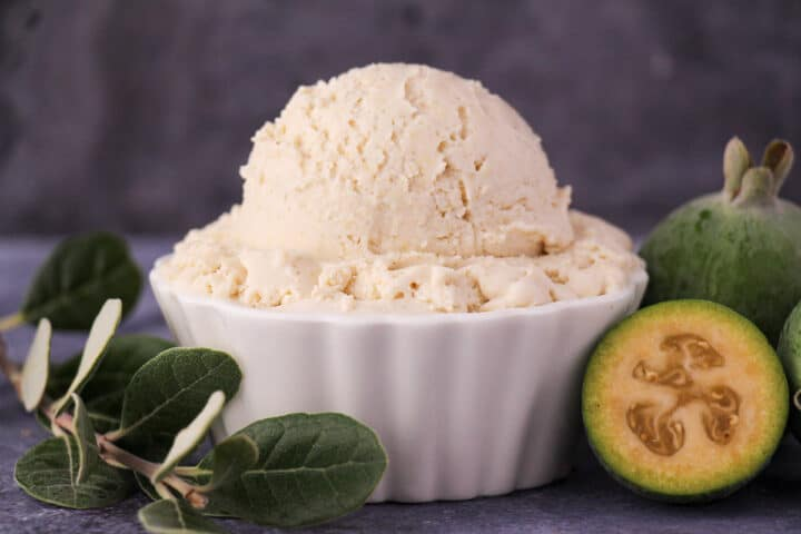Scoop of feijoa ice cream with fresh feijoa, cut in half feijoa and sprig of feijoa leaves.