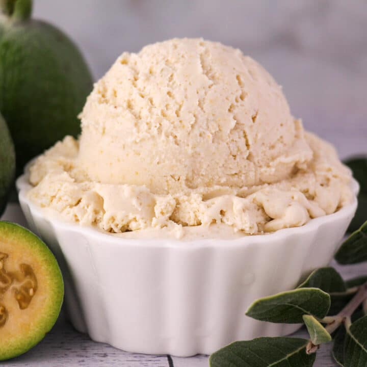 Close up scoop of feijoa ice cream with fresh feijoa, cut in half feijoa and sprig of feijoa leaves.
