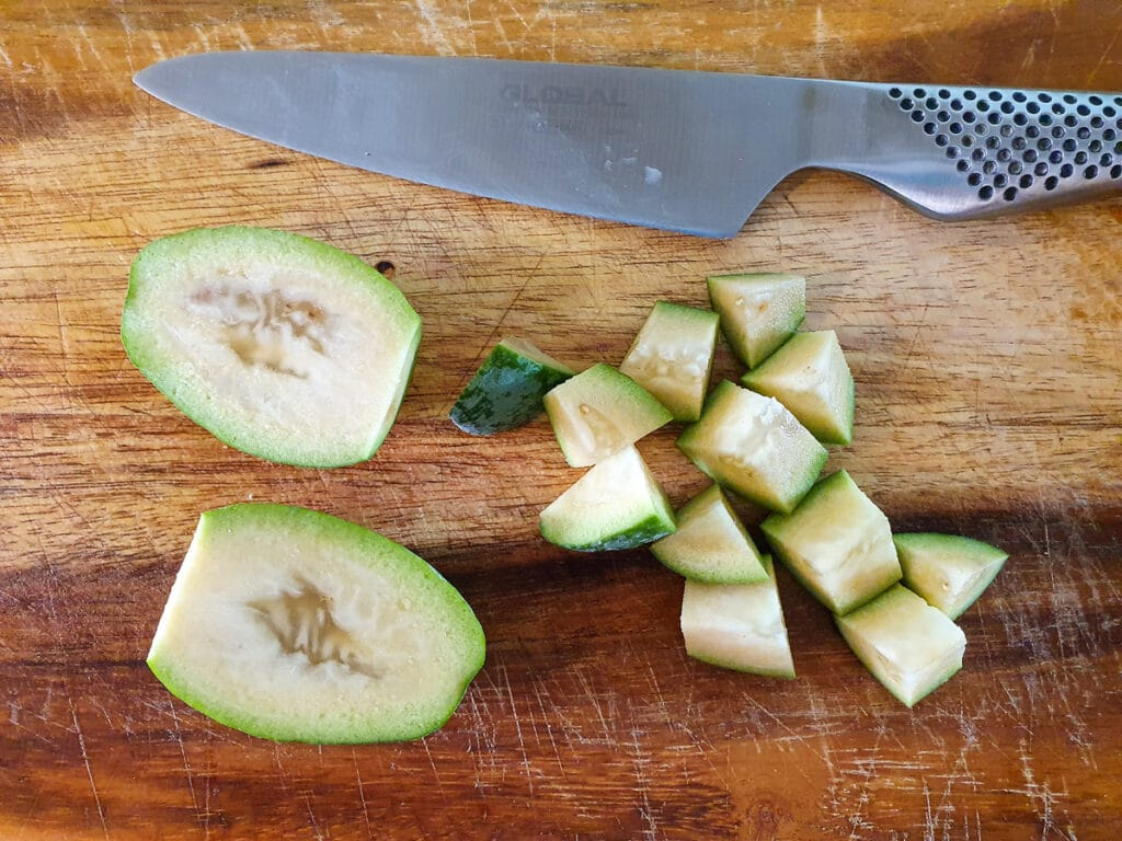 Chopping up whole feijoa with skin on.