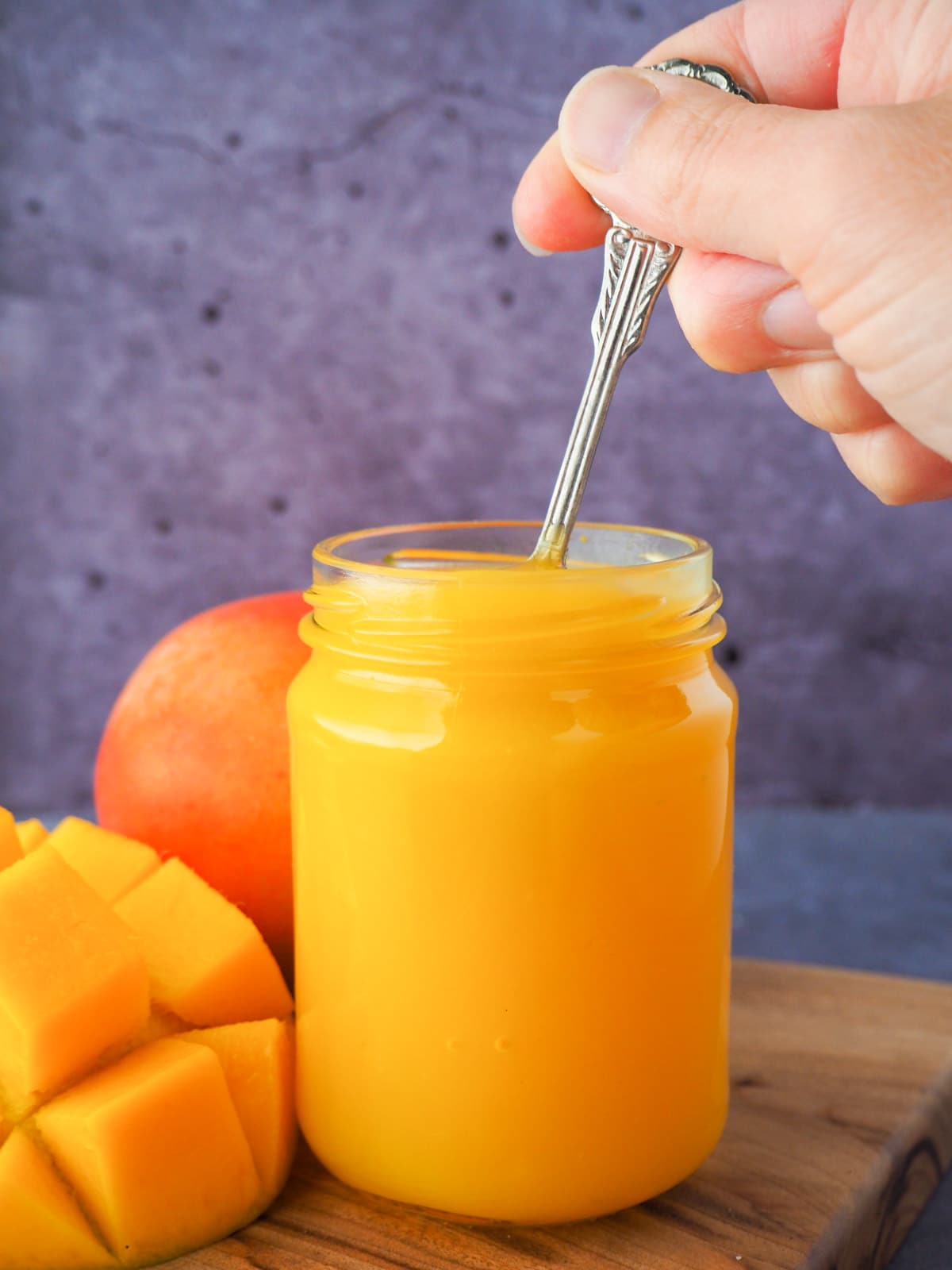 Glass jar of mango coulis with a hand holding a spoon in the jar, with fresh mango on the side.