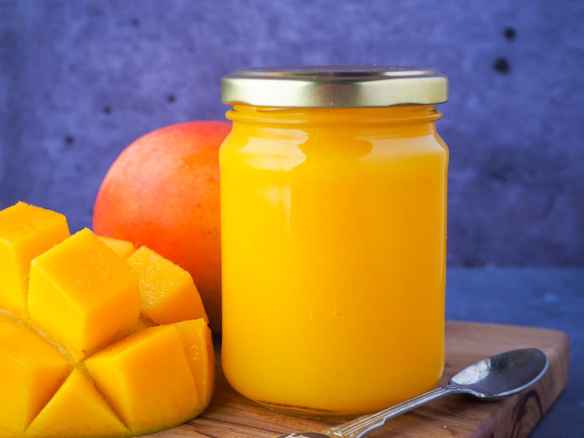 Glass jar of mango coulis with fresh mango and a vintage spoon on the side.