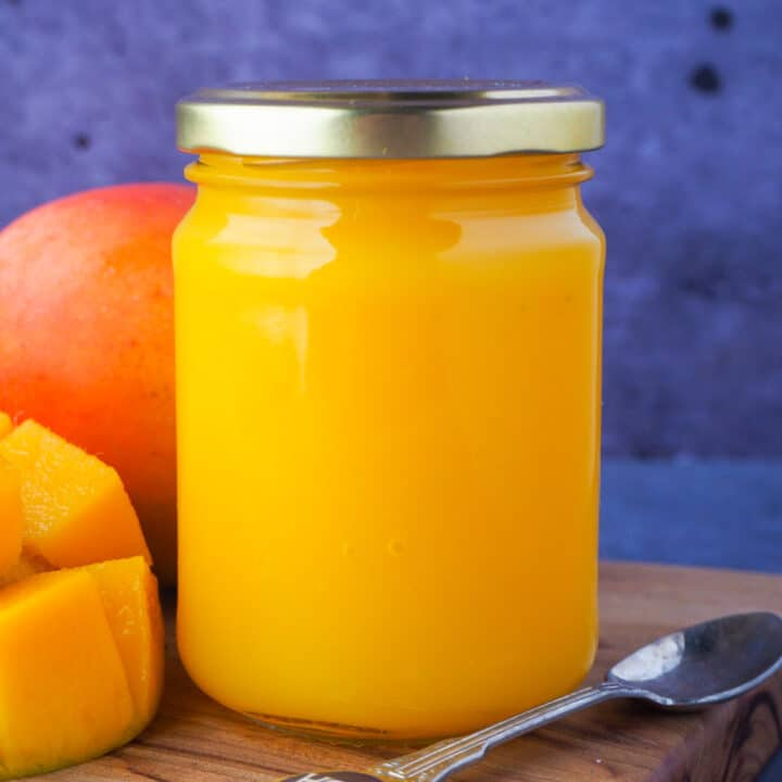 Close up closed glass jar of mango coulis with fresh mango and a vintage spoon on the side.