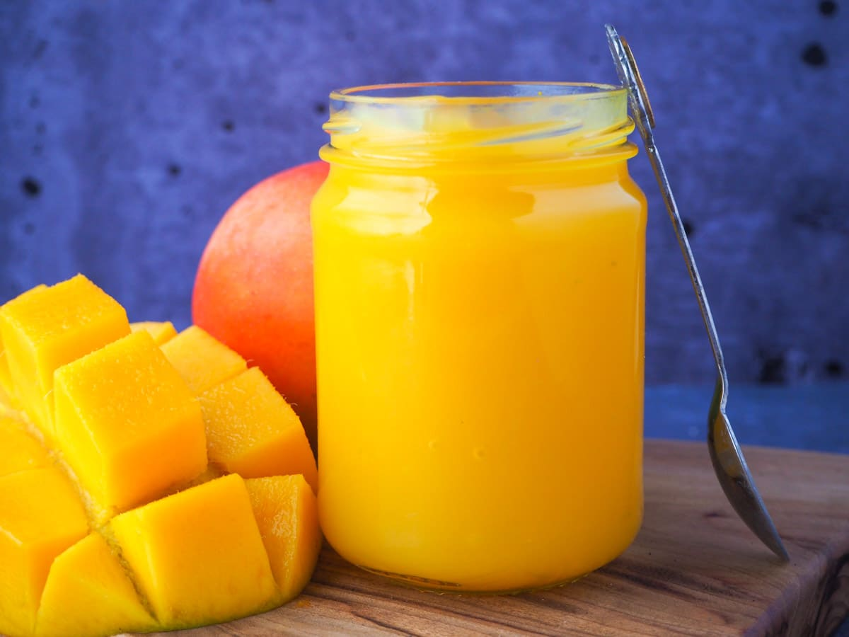 Open glass jar of mango coulis with fresh mango and a vintage spoon propped on the side.