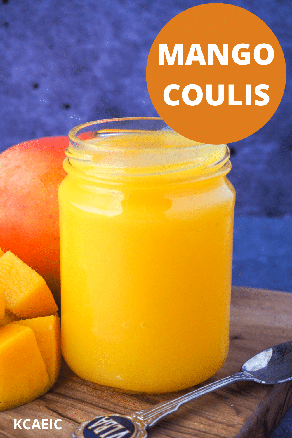 Open glass jar of mango coulis with fresh mango and a vintage spoon on the side, with text overlay, mango coulis and KCAEIC.