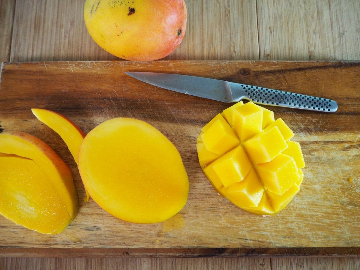 Slicing mangoes to remove flesh.