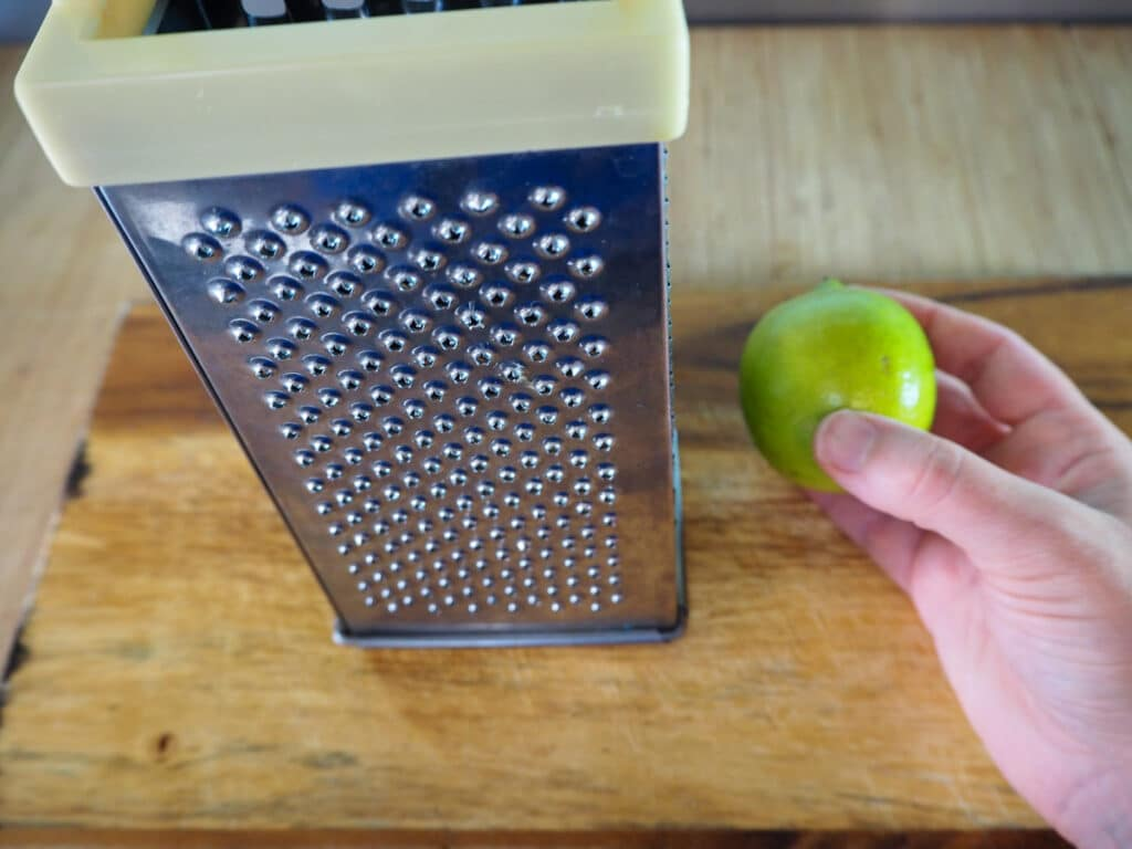 Zesting the lime with a box grater.