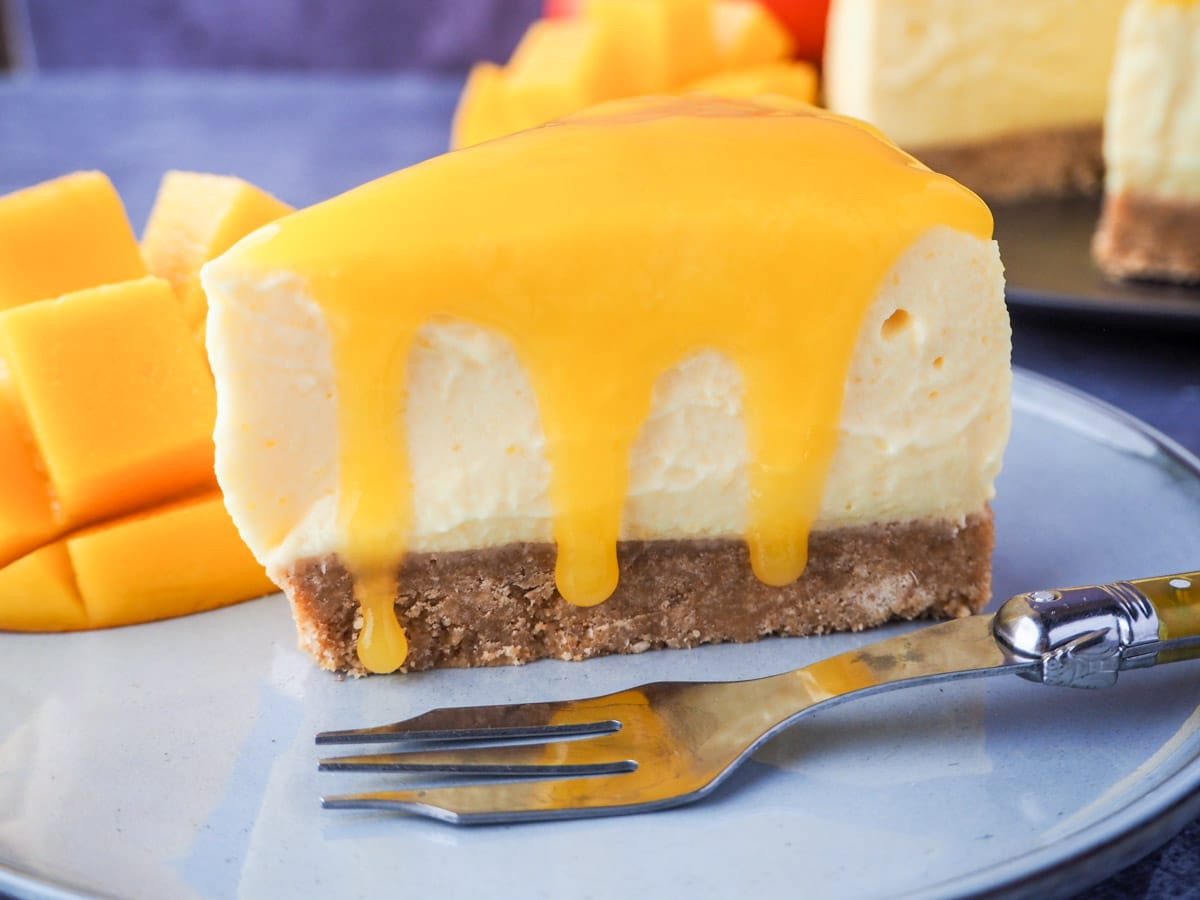 Slice of mango cheesecake with mango coulis oozing over the sides, on a plate with a vintage fork, fresh mango and the rest of the cheesecake in the background.