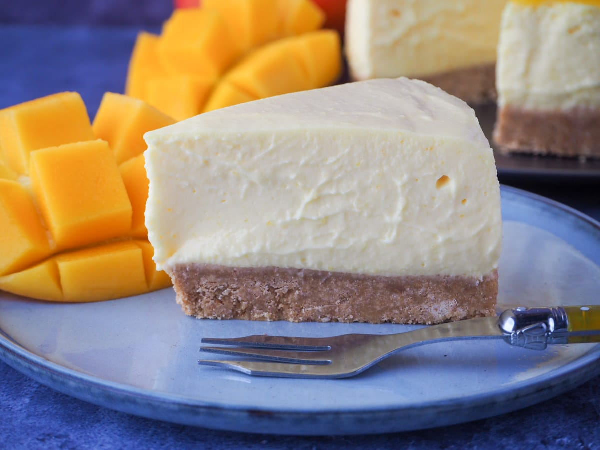 Slice of no bake mango cheesecake with a vintage fork and fresh mango on the side.
