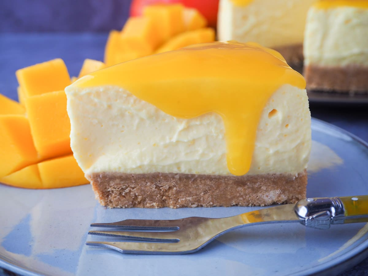Slice of no bake mango cheesecake with mango coulis, a vintage fork and fresh mango on the side.