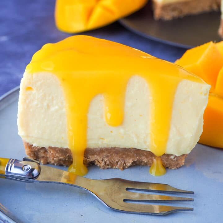Close up slice of no bake mango cheesecake with mango coulis, a vintage fork and fresh mango on the side.
