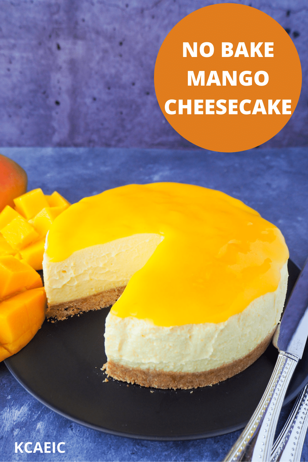 No bake mango cheesecake with a single slice cut out, mango coulis, fresh mango and silver serving wear, with text overlay, no bake mango cheesecake and KCAEIC.