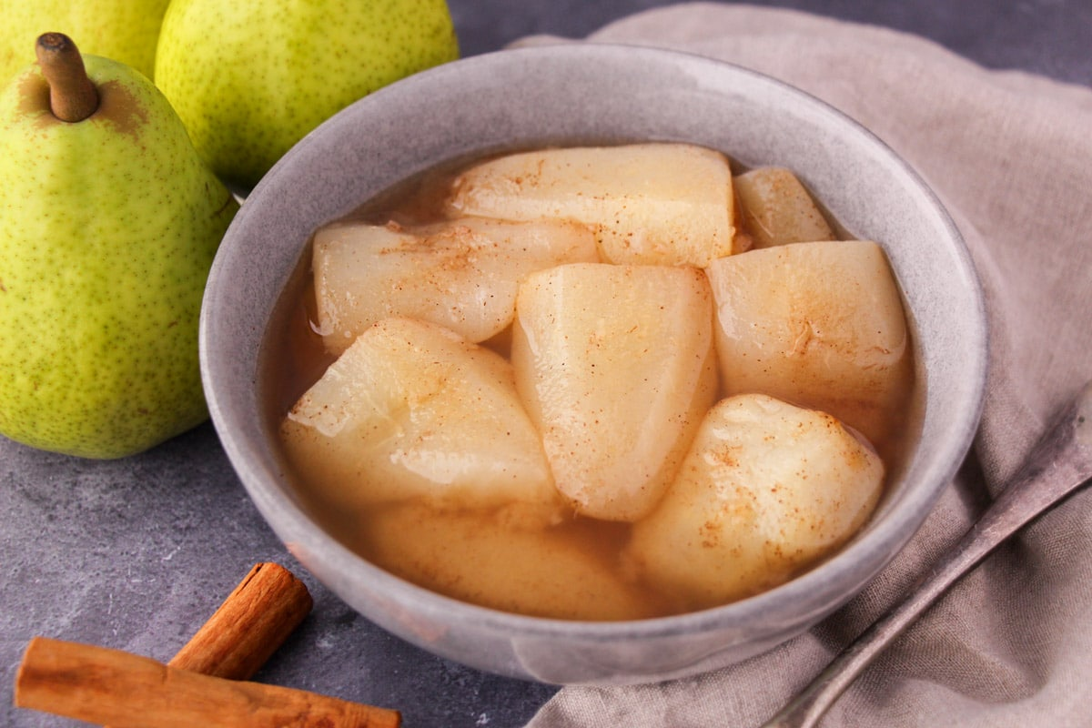 Stewed pears in a bowl, with fresh pears, cinnamon sticks and a vintage serving spoon on the side.