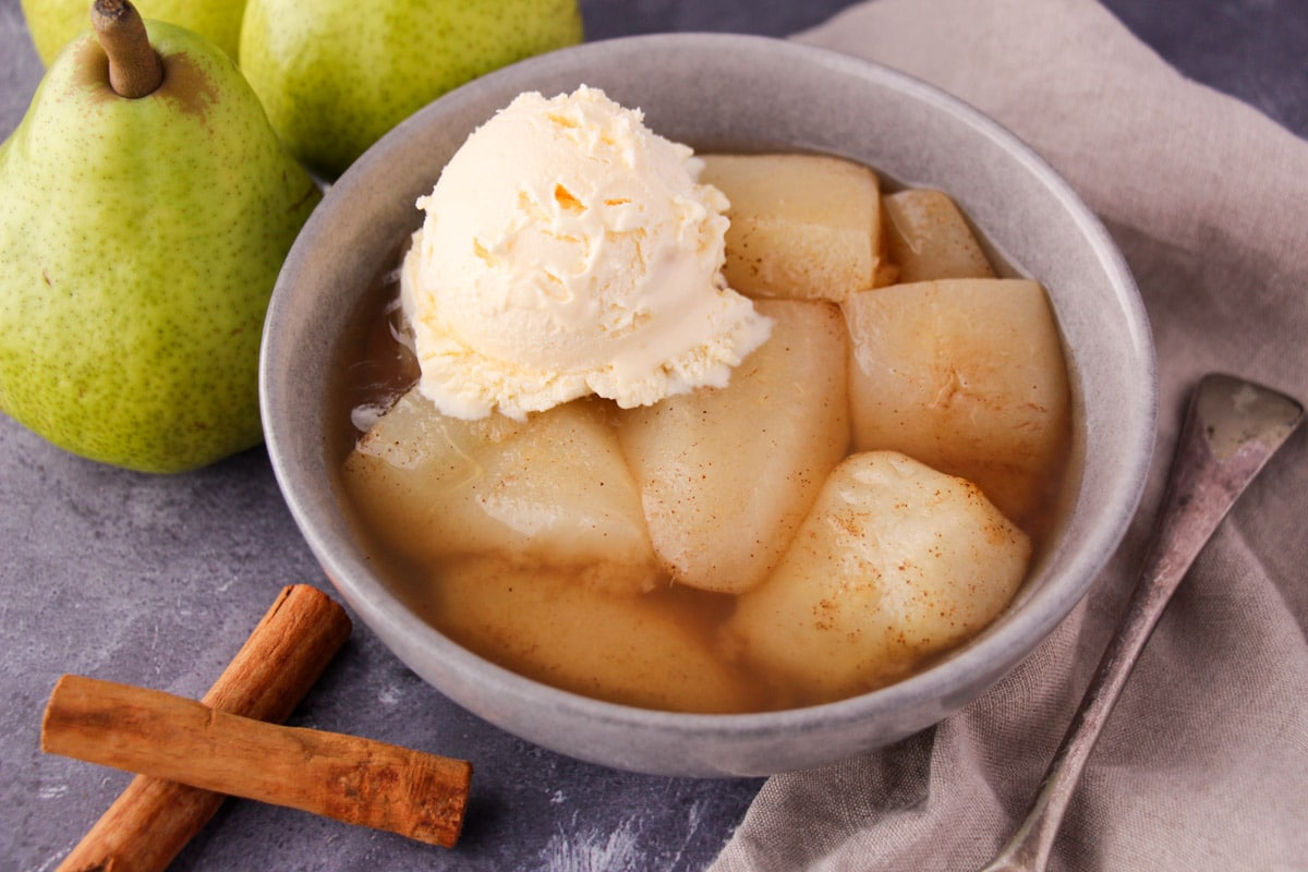 Stewed pears in a bowl with a scoop of vanilla ice cream, with fresh pears, cinnamon sticks and a vintage serving spoon on the side.
