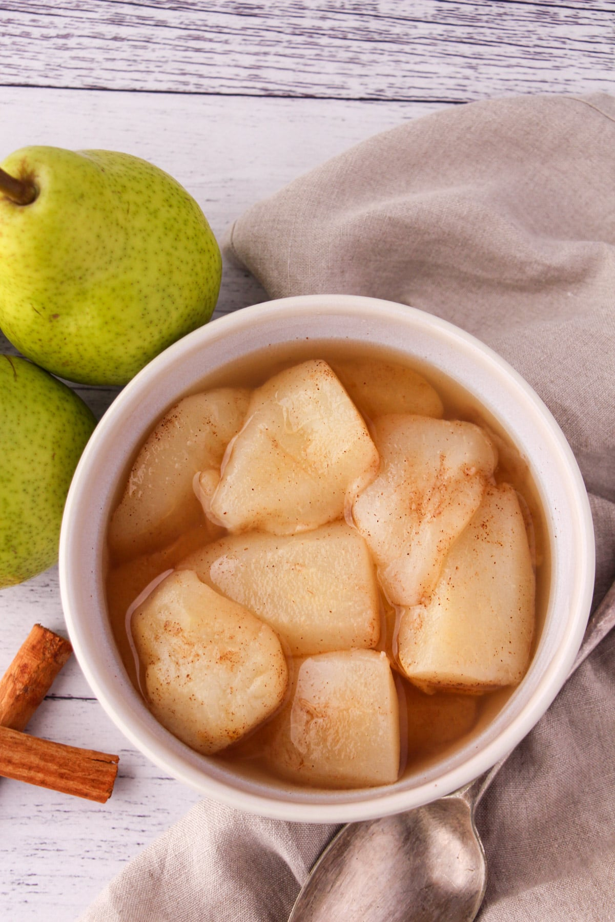 Stewed pears in a bowl, with fresh pears, cinnamon sticks and a vintage serving spoon on the side,