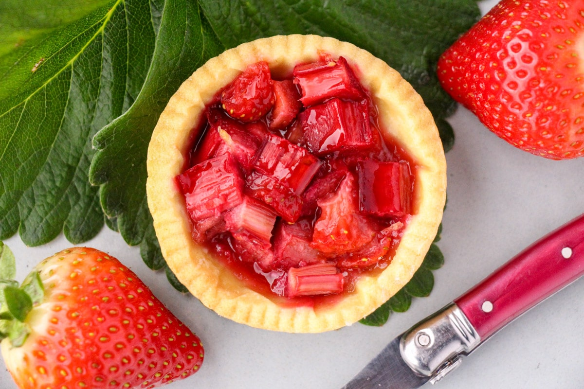 Close up strawberry rhubarb tartlets with strawberry leaves and fresh strawberries and a vintage cake fork on the side.