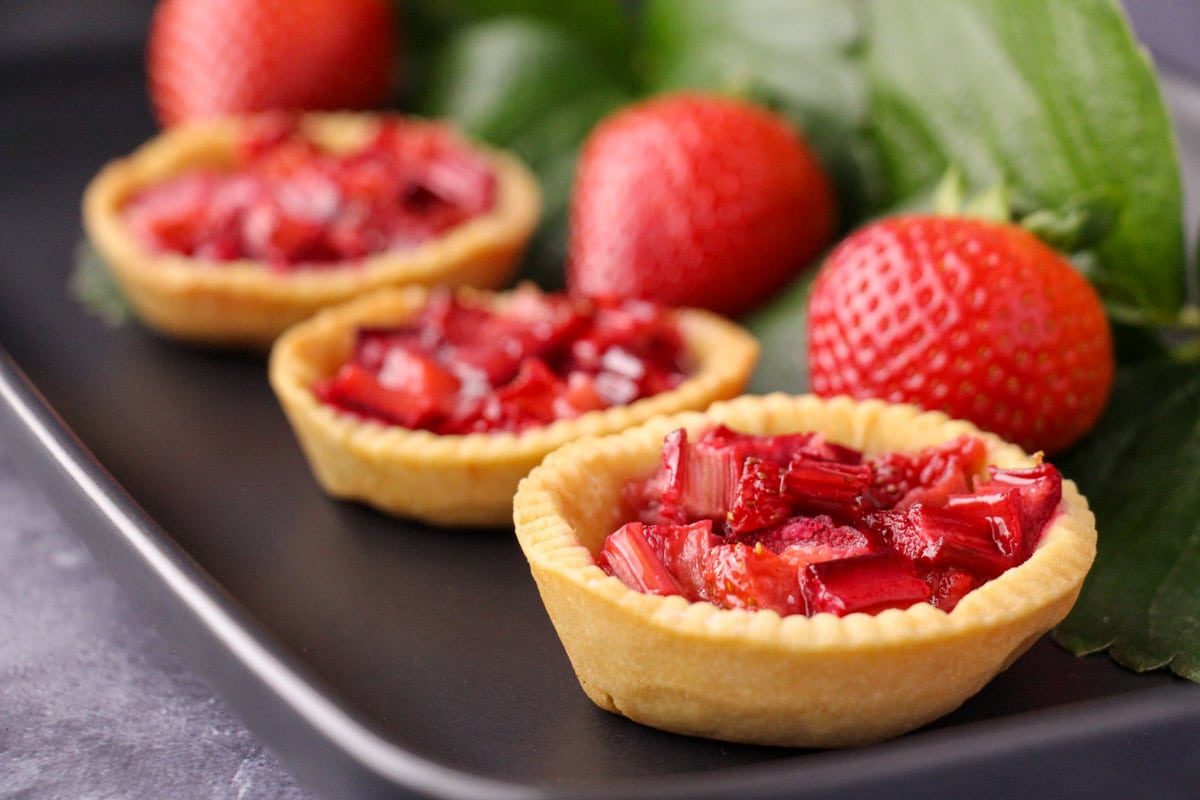 Row of strawberry rhubarb tartlets on a black serving plate, with fresh strawberries and strawberry leaves on the side.