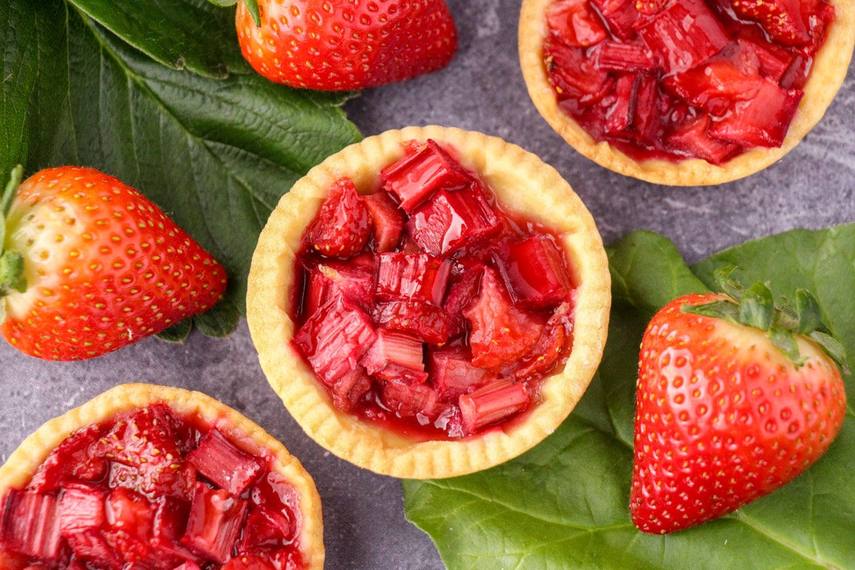 Close up strawberry rhubarb tartlets with strawberry and rhubarb leaves and fresh strawberries.