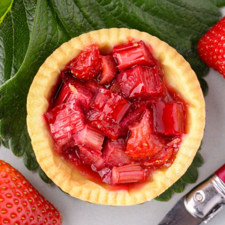 Close up strawberry rhubarb tartlets with strawberry leaves and fresh strawberries on the side.
