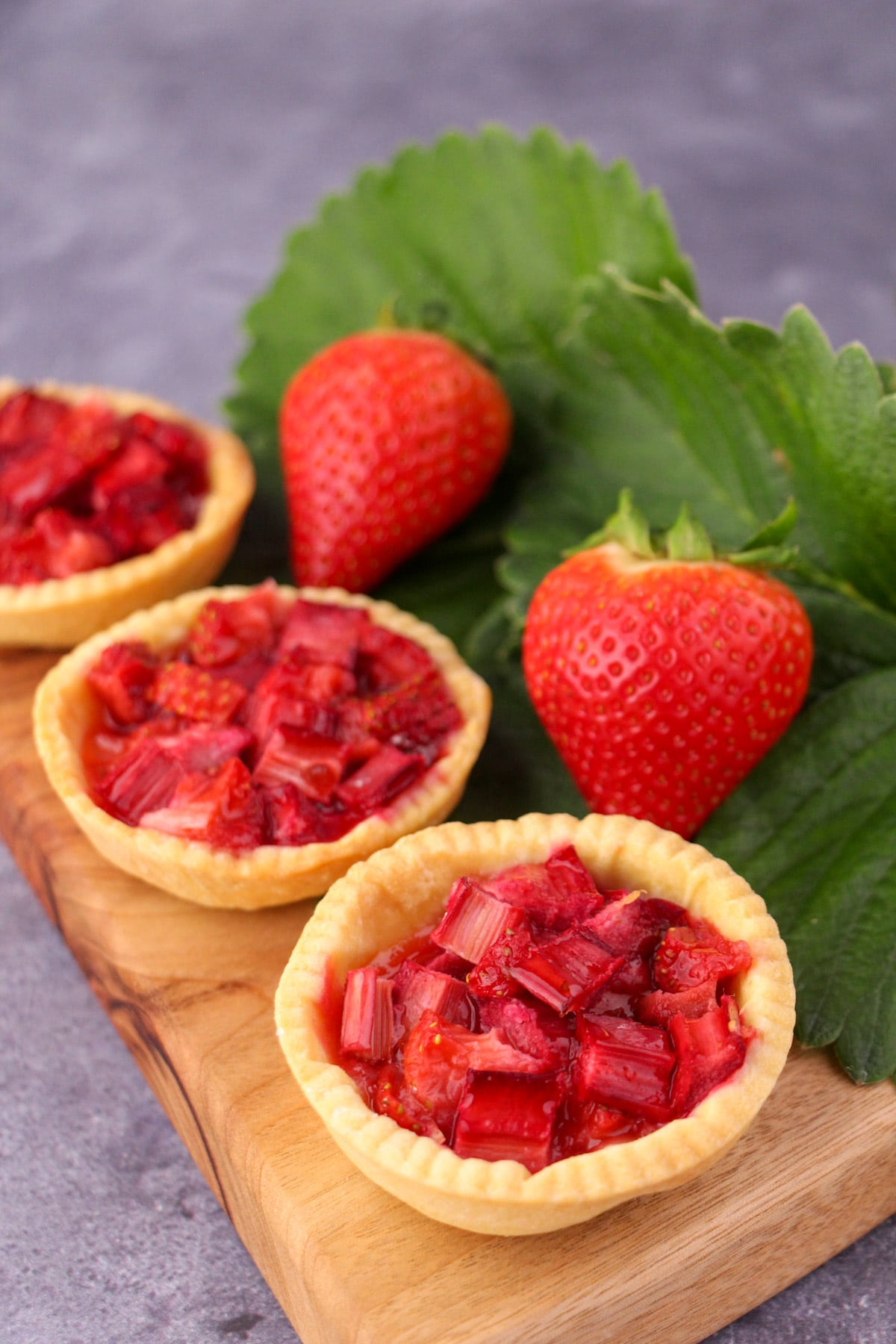 Row of strawberry rhubarb tartlets on a chopping board, with fresh strawberries and strawberry leaves on the side.
