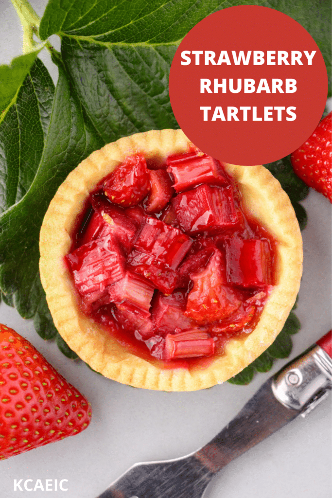 Close up strawberry rhubarb tartlets with strawberry leaves and fresh strawberries and a vintage cake fork on the side, with text overlay, strawberry rhubarb tartlets and KCAEIC.