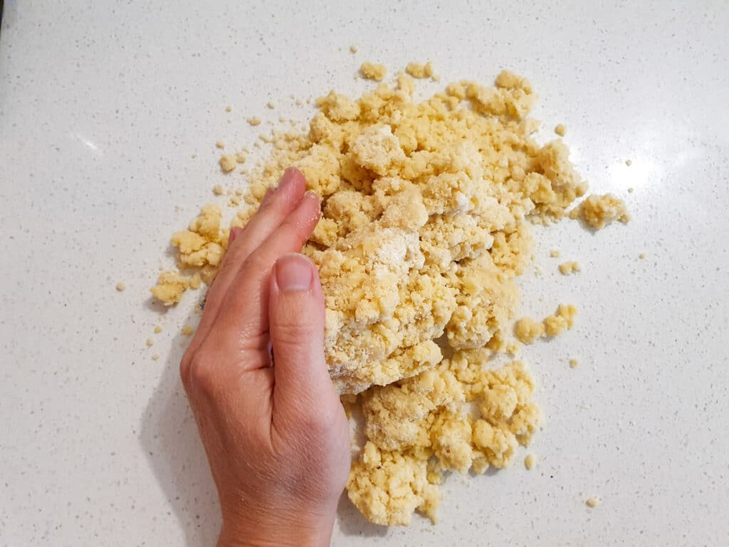 Pushing together dough with hands to form a disk.