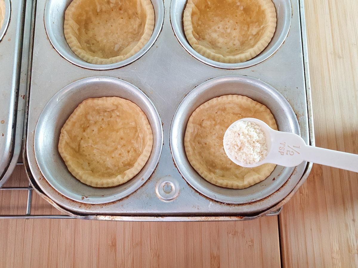 Adding almond flour to tartlet cases.