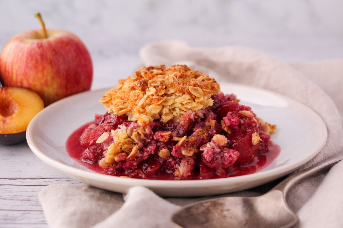Apple and plum crumble on a plate with vintage serving spoon and fresh fruit in the back ground