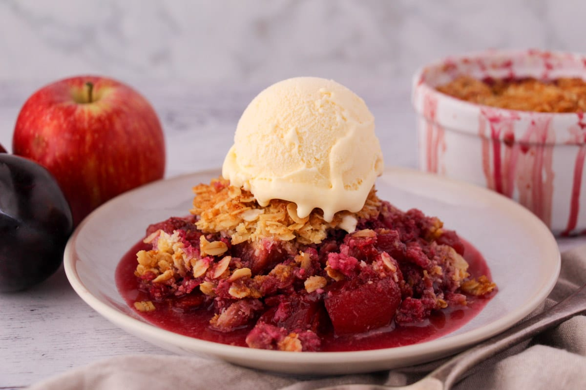 Apple and plum crumble on a plate with ice cream, with vintage serving spoon and ramakin and fresh fruit in the back ground