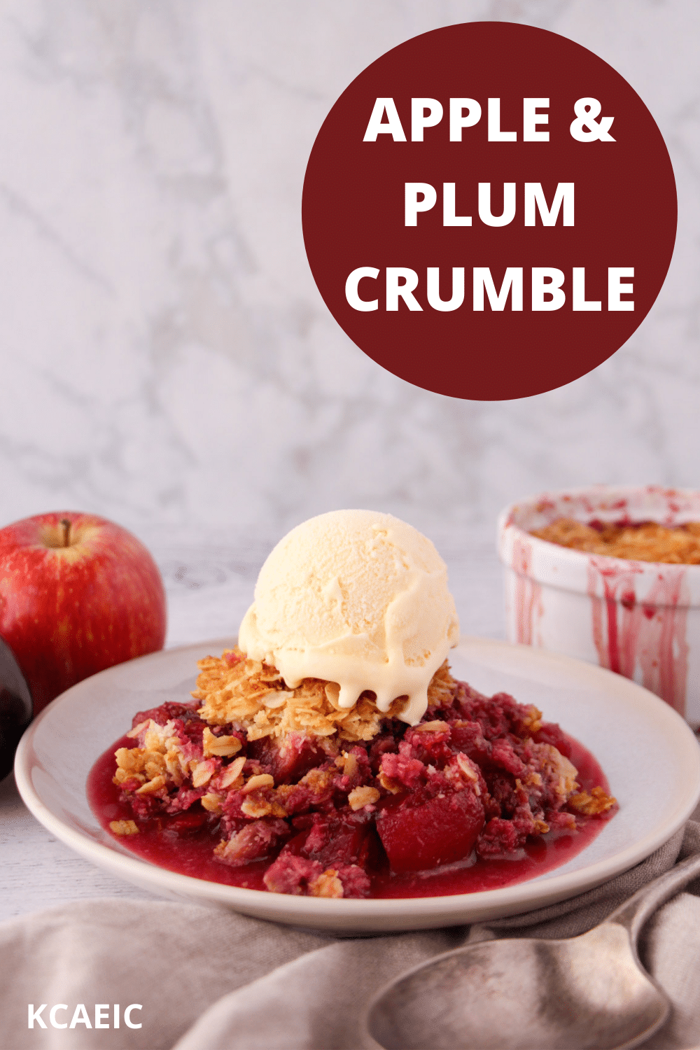 Apple and plum crumble on a plate with ice cream, with vintage serving spoon and ramakin and fresh fruit in the back ground and text overlay, apple and plum crumble and KCAEIC.
