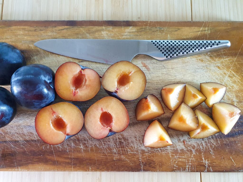 Cutting open plums, removing stones then quartering each half.