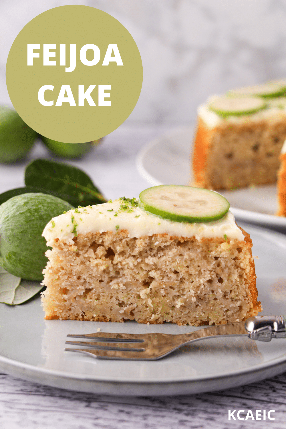 Slice of feijoa cake on a plate with a cake fork, the rest of the cake and fresh feijoas and leaves in the background, with text overlay, feijoa cake and KCAEIC.